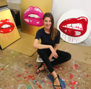Artist Sara Pope sitting in studio with lip paintings