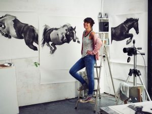 Patsy McArthur standing on ladder in her art studio with her charcoal drawn horse pieces hung on the wall