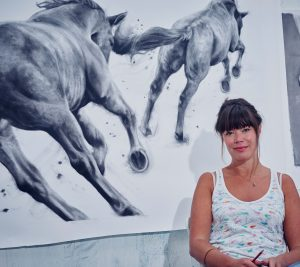 Patsy McArthur sitting in front of one of her charcoal drawn horse pieces in her art studio